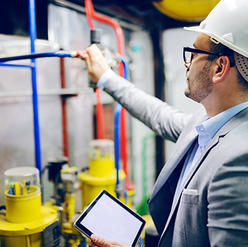 Handsome caucasian supervisor in suit and with helmet on head holding tablet and checking on boiler in factory.